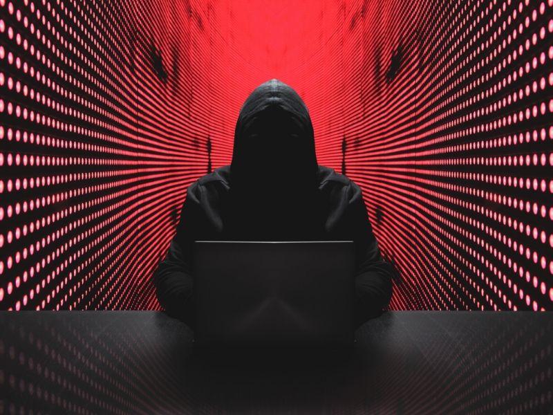 hacker in black hoodie against red server background